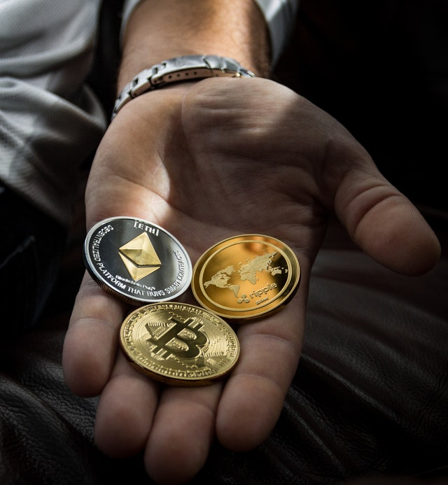 Cryptocurrency Coins in Man's Hand