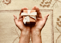 hands giving a gift box